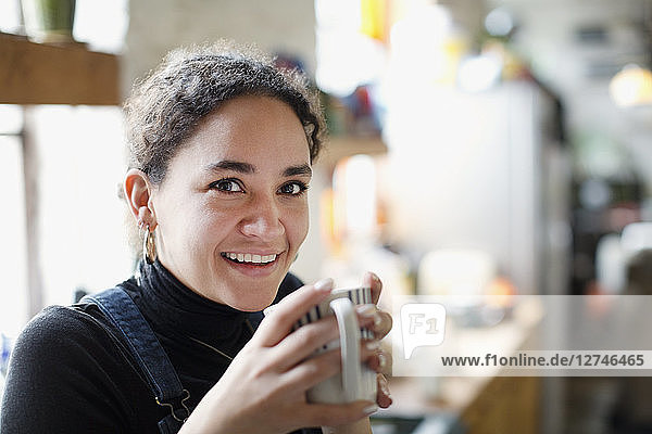 Portrait smiling young woman drinking coffee