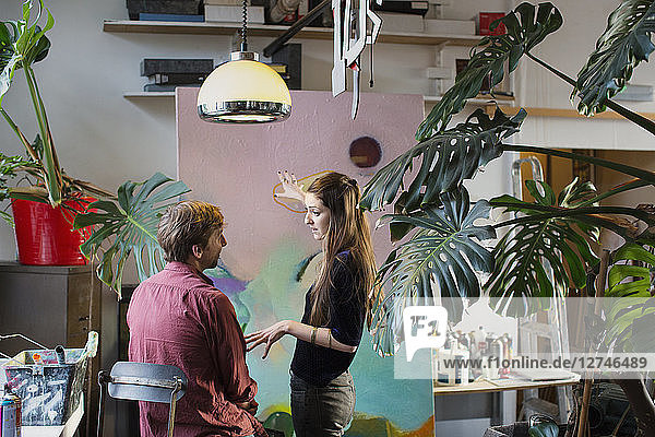 Artists discussing painting in apartment