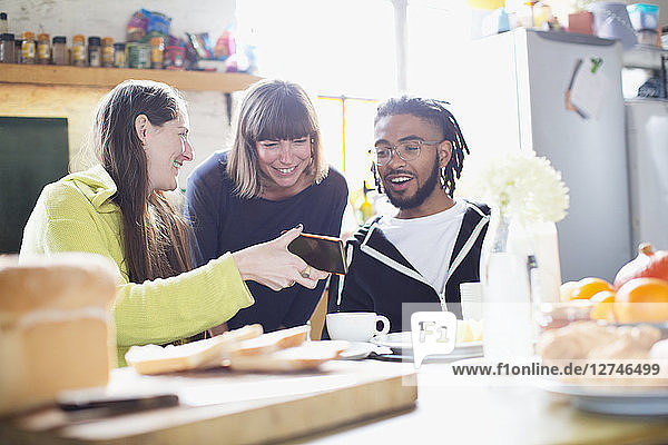 Young roommate friends using smart phone at breakfast table in apartment