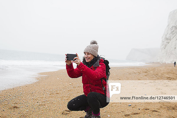 Woman in warm clothing using camera phone on snowy beach