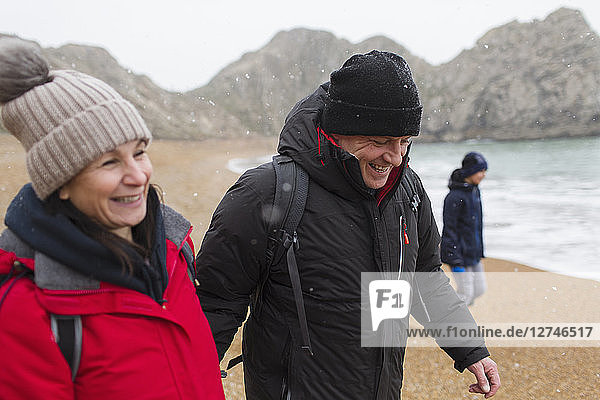 Smiling couple in warm clothing on snowy winter beach