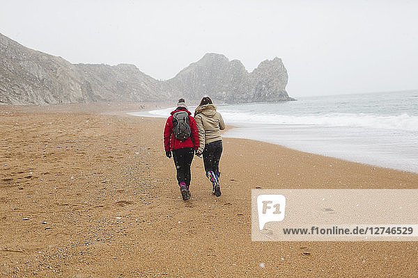 Mother and daughter in warm clothing walking on snowy winter ocean beach