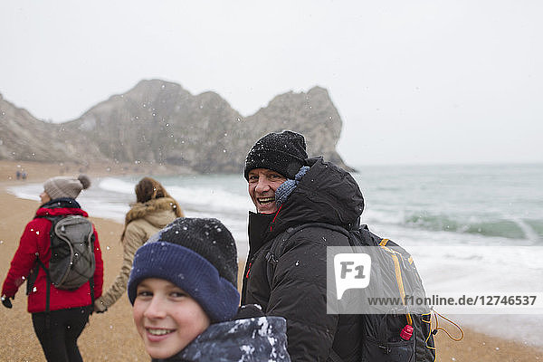 Portrait father and son in warm clothing walking on snowy winter ocean beach