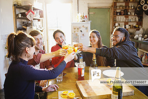 Happy young adult friends toasting cocktails at apartment kitchen table