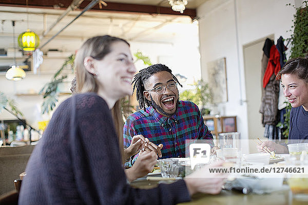Happy young adult roommates eating take out food at kitchen table in apartment
