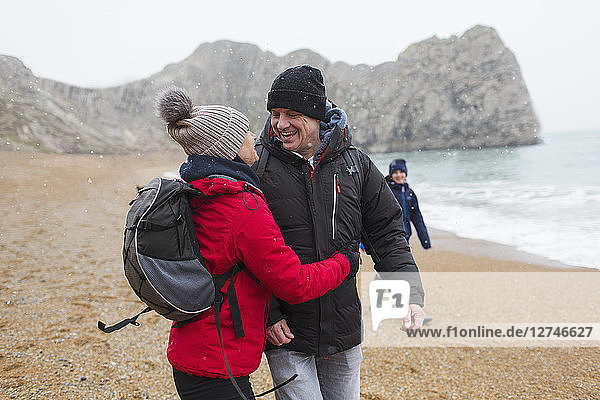 Affectionate  happy couple in warm clothing on snowy winter beach