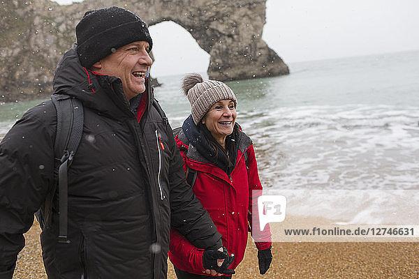 Happy couple in warm clothing walking on snowy ocean beach