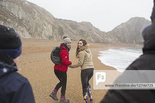 Family walking on snowy winter beach