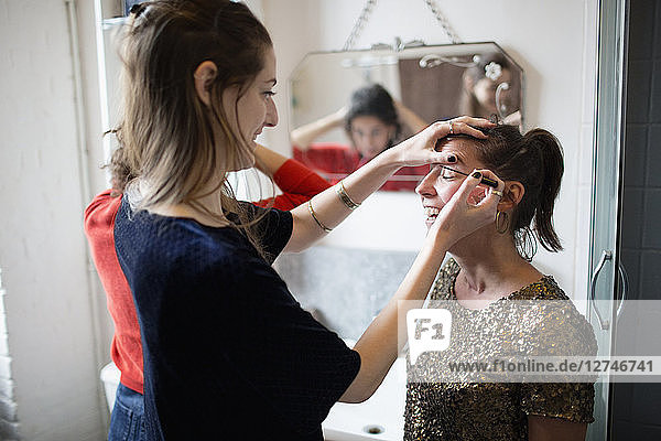 Young women getting ready  applying makeup in bathroom