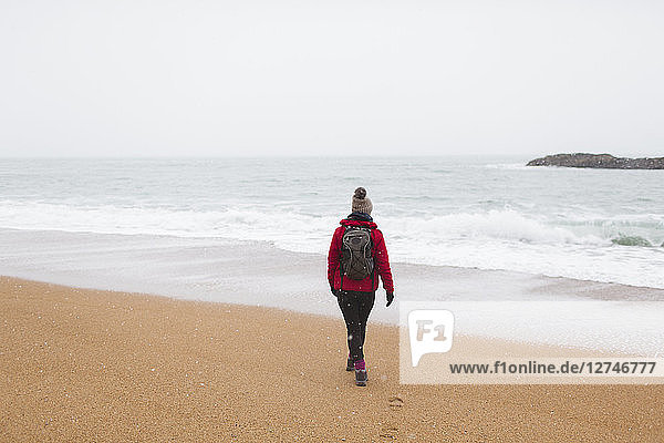 Woman with backpack walking on winter beach