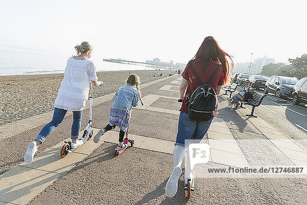 Lesbian couple with daughter riding push scoters on sunny beach boardwalk