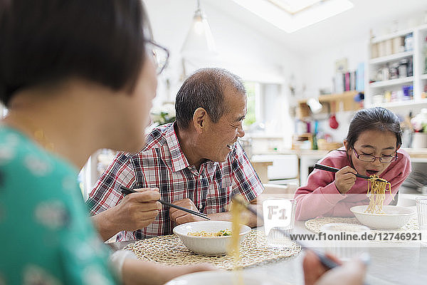 Multi-generation family eating noodles with chopsticks at table
