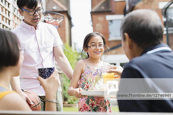 Granddaughter serving orange juice to grandfather in backyard
