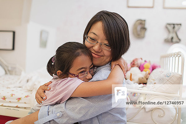 Affectionate mother and daughter hugging in bedroom