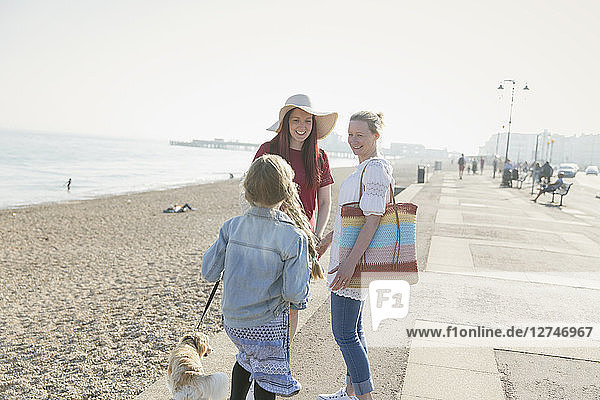 Lesbian couple with daughter and dog on sunny beach boardwalk