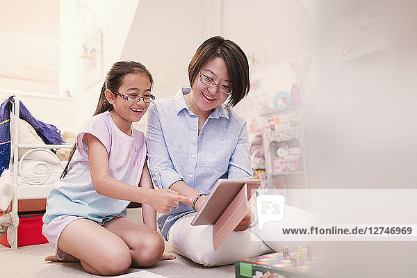 Mother and daughter using digital tablet on bedroom floor
