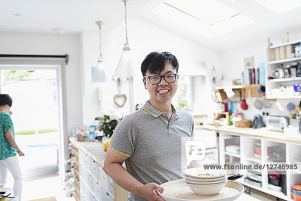 Portrait smiling man doing dishes in kitchen