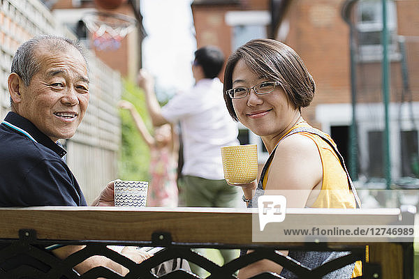 Portrait smiling daughter and senior father drinking tea on bench in yard