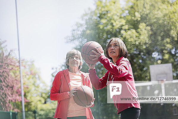 Active senior women friends playing basketball in sunny park