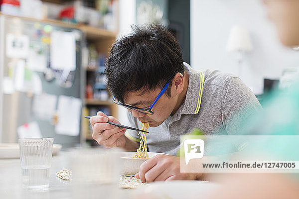 Man eating noodles with chopsticks at table