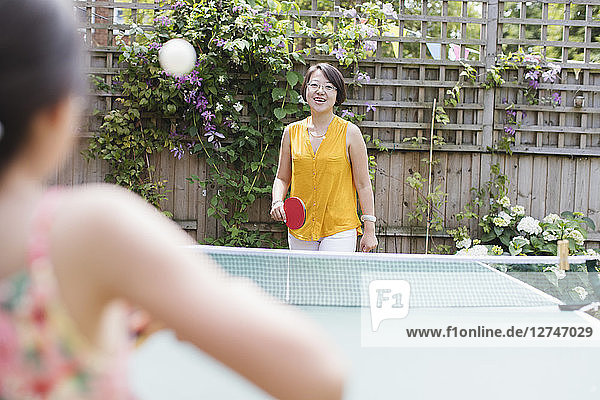 Mother and daughter playing table tennis in sunny backyard