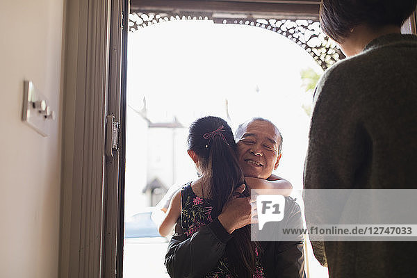 Affectionate granddaughter greeting and hugging grandfather in doorway
