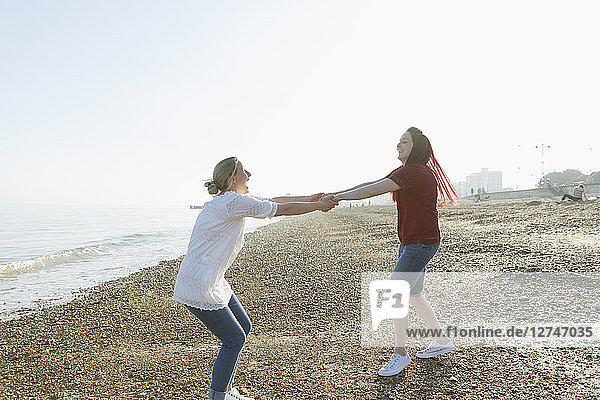 Playful lesbian couple holding hands and spinning on sunny beach