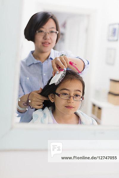 Mother brushing daughters hair in bathroom mirror