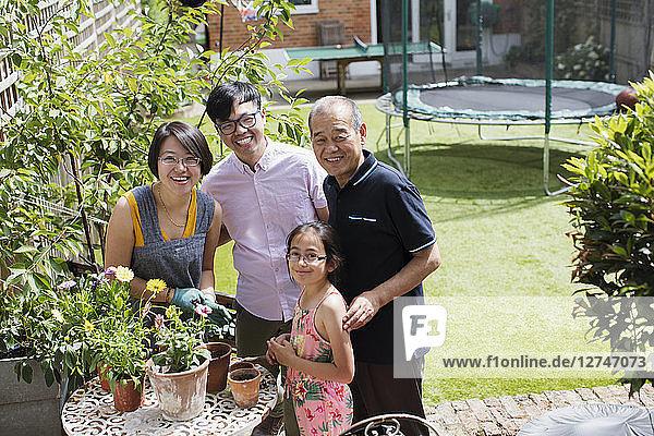 Portrait smiling multi-generation family gardening  potting flowers in sunny yard
