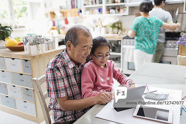 Grandfather and granddaughter using digital tablet in kitchen