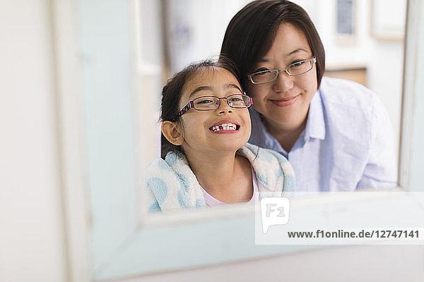 Mother watching daughter showing teeth in bathroom mirror
