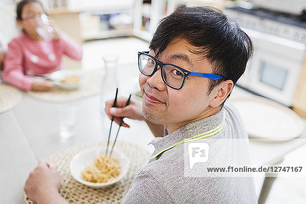 Portrait smiling man eating noodles with chopsticks at table