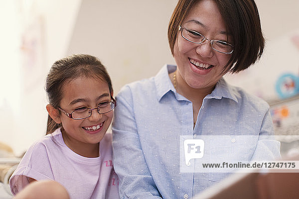 Smiling mother and daughter reading