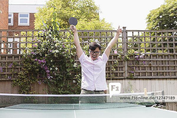 Exuberant man playing table tennis  celebrating