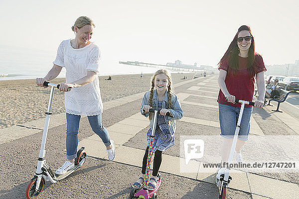 Lesbian couple and daughter riding push scooters on sunny beach