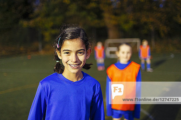 Portrait confident girl playing soccer