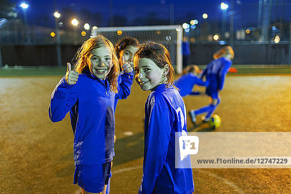 Portrait confident girl playing soccer  gesturing thumbs-up