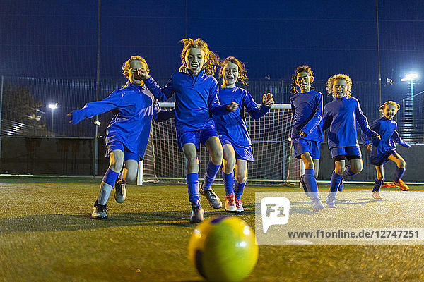 Girls soccer team playing  running toward ball on field at night