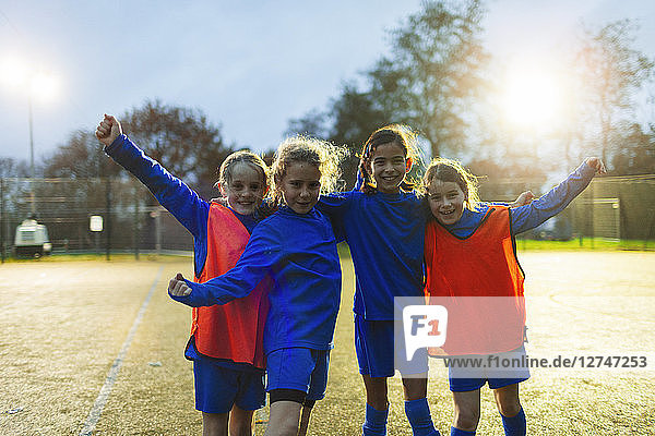 Portrait confident girls soccer team cheering on field