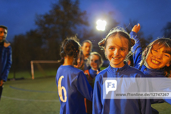 Portrait confident  happy girl soccer players on field at night