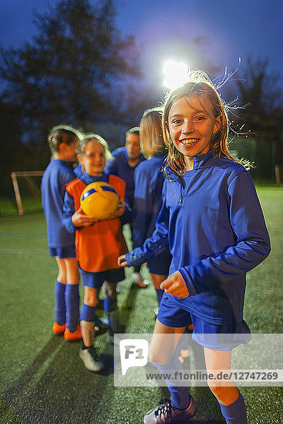 Portrait smiling  confident girl soccer player practicing with team on field at night
