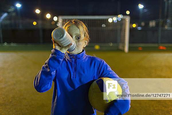 Girl soccer player taking a break  drinking water on field at night