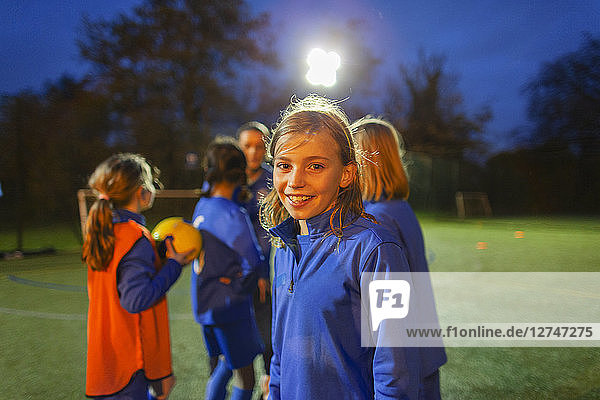 Portrait smiling  confident girl soccer player on field at night