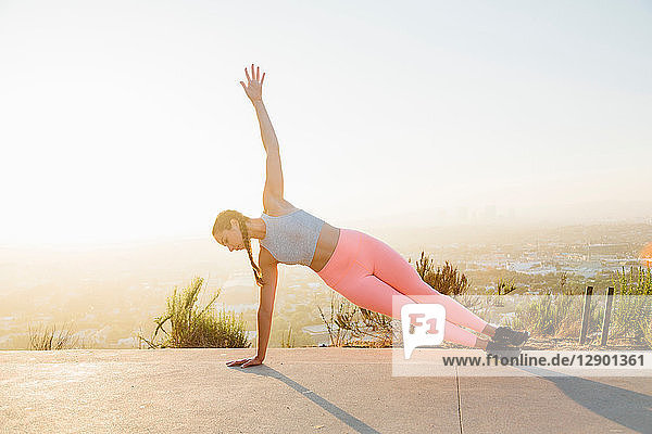 Woman in plank position on hilltop