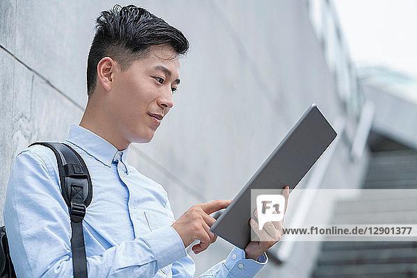 Junger Geschäftsmann benutzt digitales Tablet auf einer Stadttreppe  Shanghai  China