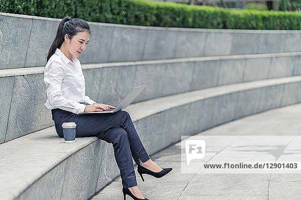 Young businesswoman typing on laptop on city seat  Shanghai  China