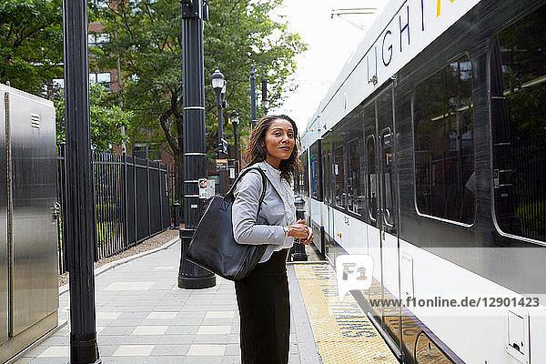 Businesswoman on platform by train