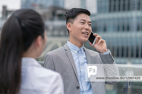 Young businesswoman and man talking on smartphone in city  Shanghai  China