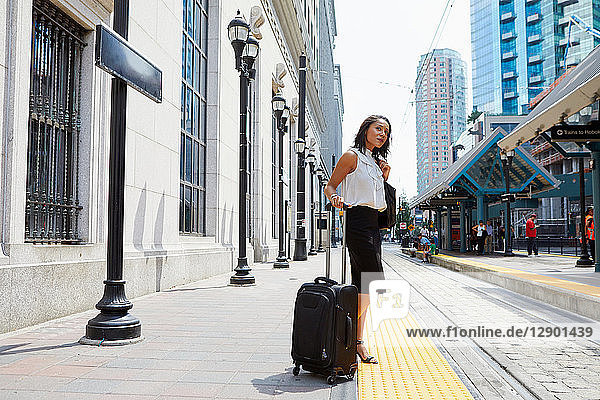 Geschäftsfrau wartet auf Stadtbahnsteig