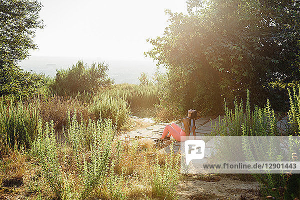 Woman relaxing among shrubs on hilltop